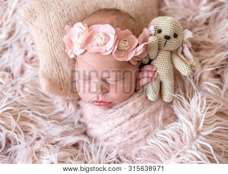 Adorable newborn lying in bed with favorite knitted toy