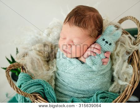 Cute newborn boy wrapped in a blanket sleep inside the basket with the toys