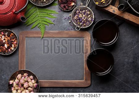 Set of different herbal and fruit dry teas on stone table. Top view flat lay with copy space