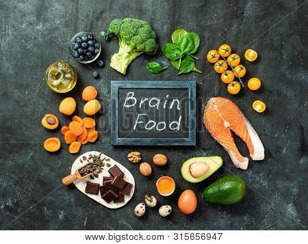 Brain Food Concept With Copy Space In Center. Various Food Ingredients For Thought And Chalkboard Wi