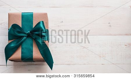 Gift Box In Craft Wrapping Paper And Green Satin Ribbon On White Wooden Table, Copy Space Right. Bea