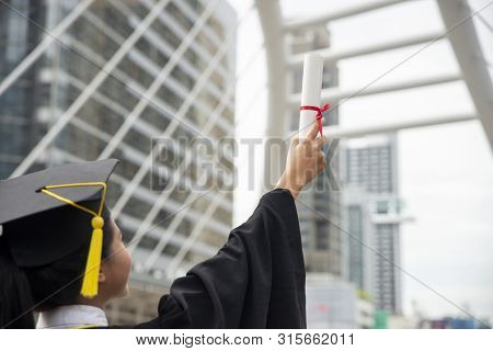 Happy Asian Student Woman Winning Graduate Diploma And Mba Degree In College,wearing Academic Dress