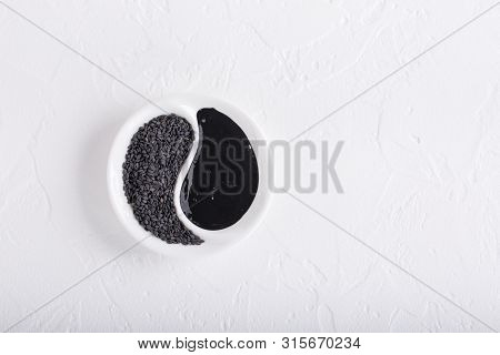 Black Tahini Sauce And Black Sesame Seeds On White Background. Natural Paste Made From Sesame Seeds.