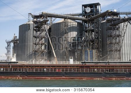 Loading Grain On A Ship In The Port. View From The River To The Port Infrastructure, Grain Storage T