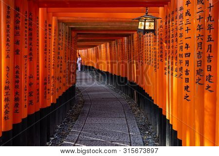 KYOTO, JAPAN, APRIL 01, 2019 : A woman is posing in traditional costume inside the torii tunnel of the Fushimi Inari shrine