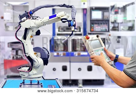 Engineer Check And Control Automation Orange Modern Robot System In Factory, Industry Robot Concept