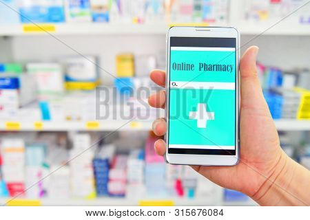 Hand Holding Mobile Smart Phone For Search Bar On Display In Pharmacy Drugstore Shelves Background.o