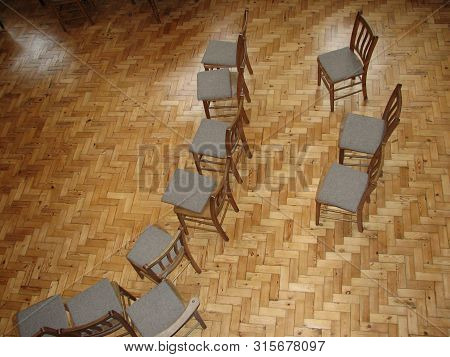Scattered Chairs In Rows On Wooden Floor
