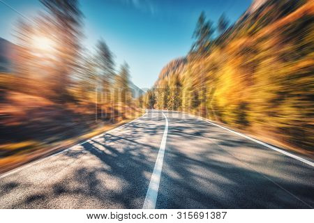 Mountain Road In Autumn Forest At Sunset With Motion Blur Effect. Asphalt Road And Blurred Backgroun