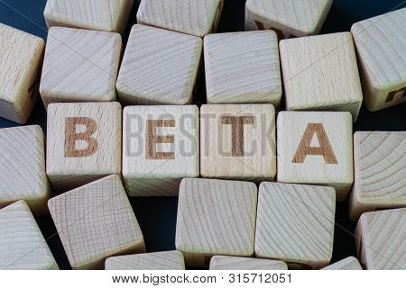 Beta coefficient or measure of volatility and risk of an individual stock compare to unsystematic risk in stock market concept, cube wooden block with alphabet combine the word Beta. poster