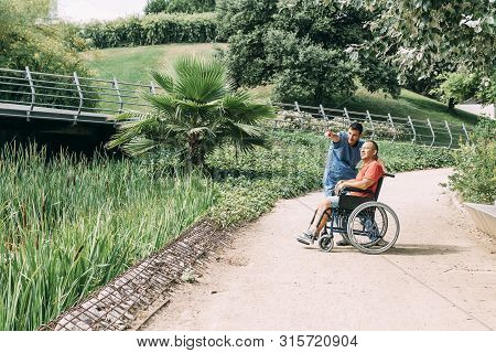 Caretaker Talking With His Disabled Patient In A Wheelchair During A Walk, Concept Of Medical Care A