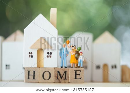 Miniature People: Family Stand On Wood Block Words Home And House Background. The Concept Of Family