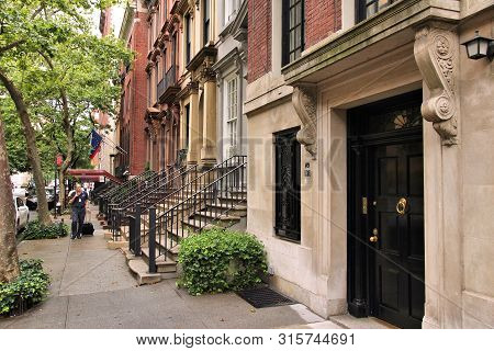 New York, Usa - July 3, 2013: People Walk By New York Brownstone Townhouses In Turtle Bay Neighborho