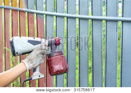 Painting Metal Fence Spray. Man Paints A Fence With A Paint Sprayer