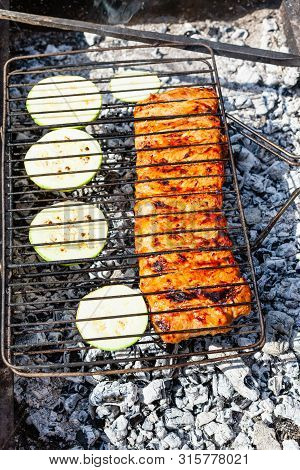 Cooking Raw Pork Ribs Marinated In Sauce With Sliced Squash Vegetable In Outdoor Charcoal Grill