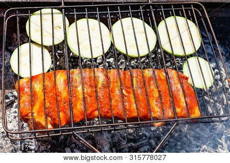 Raw Pork Ribs Marinated In Sauce With Sliced Zucchini Vegetable In Outdoor Grill