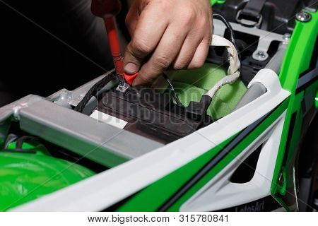 The Wizard Installs A New Battery On The Motorcycle After Refueling And Checking.