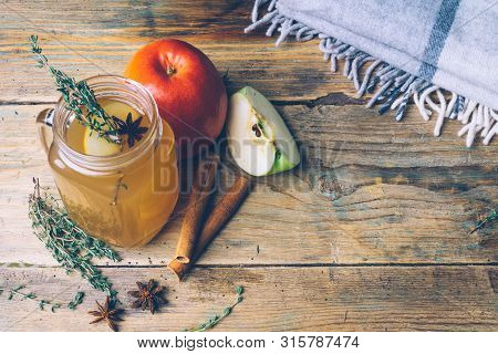 Apple Cider (mulled Cider) With Cinnamon Sticks And Fresh Apples On Wooden Background. Autumn Drinks