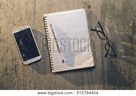 Top View Of An Old Table With Mobile, Pad, Pencil And Glasses