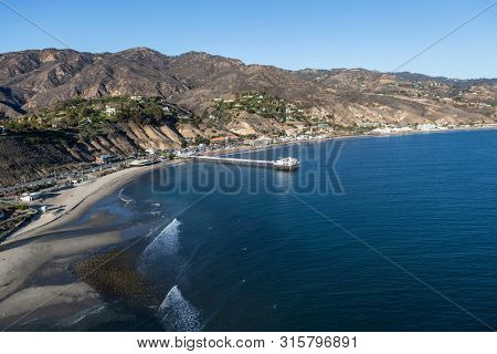 Aerial of Surfrider Beach, Malibu Pier and the Santa Monica Mountains north of Los Angeles in Southern California.