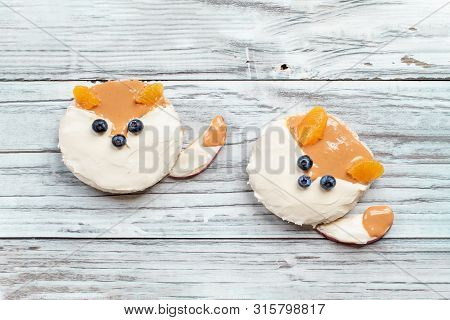 Funny Food For Kids. Rice Cakes In The Shape Of Foxes Lying On A Rustic White Table. Fox Is Made Fro