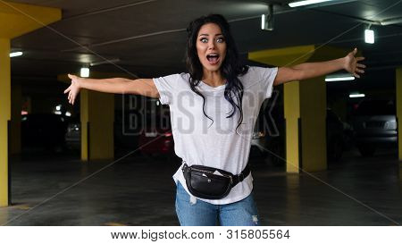 Full Of Emotion. Waist Up Portrait Of Young Woman In White T-shirt, Blue Jeans And Fanny Pack. Girl