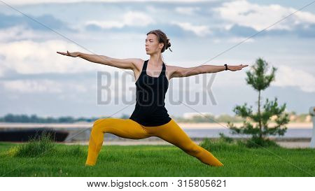 Young Woman With Trim Figure Practicing Yoga Warrior Pose. Girl Performs Yoga In A Park On Internati