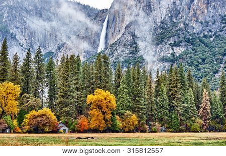 Yosemite National Park Valley with Yosemite Falls at cloudy autumn morning. Low clouds lay in the valley. California, USA.