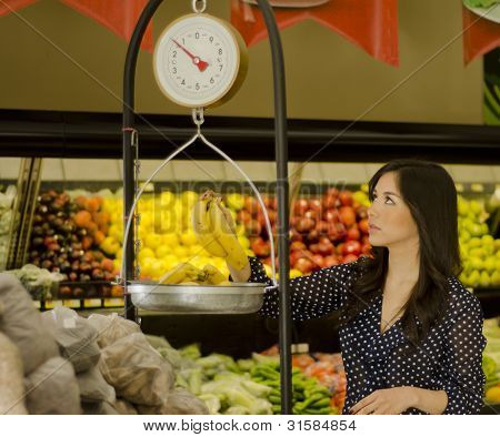 Pretty young woman weighing some fruits