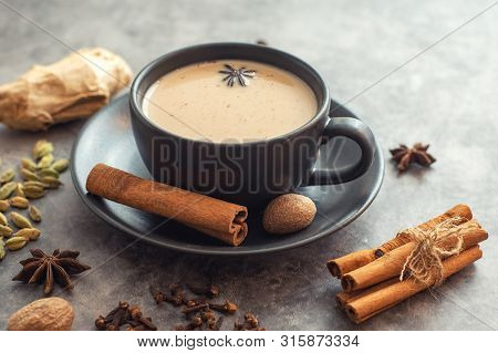 Cup Of Traditional Indian Masala Chai Tea With Ingredients. Cinnamon, Cardamom, Anise, Nutmeg.