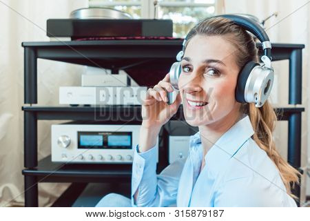 Audiophile woman enjoying music in her home looking at the camera