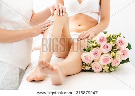 Hair removal using creme on legs of beautiful woman in beauty parlor