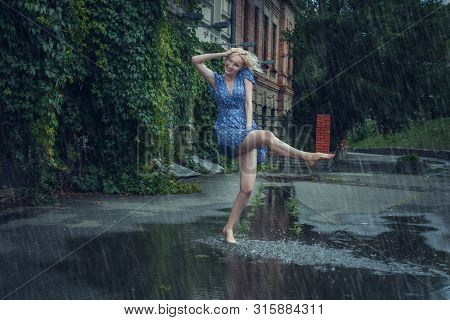 Young Woman Frolics Barefoot Through Puddles In The Summer Rain.