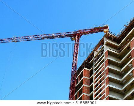 Industrial Crane Near Building Against Blue Sky. Construction Site. Red Brick Building Under Constru