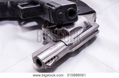 Two handguns, a silver snub nosed 357 magnum revolver and a black 9mm pistol on a white background poster