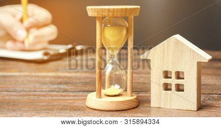 Wooden House And Clock. A Person Signs Documents. Signing A Contract To Rent A House Or Apartment. M