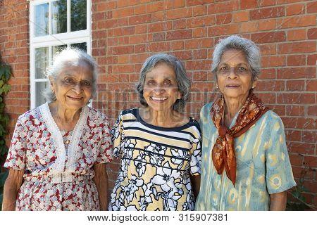 Buckingham, Uk - July 05, 2019. Three Old Elderly Indian Women (sisters, Siblings) Pose Smiling For