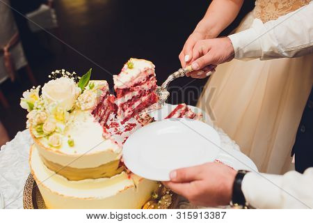 Three-tiered white wedding cake decorated with flowers from mastic on a white wooden table. Picture for a menu or a confectionery catalog with copy space. poster