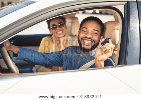 Visiting Car Dealership. Afro Couple Showing Car Key, Looking At Camera And Smiling, Sitting In New