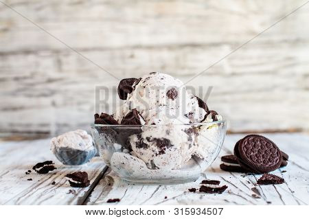 Clear Glass Bowl Of Cookies And Cream Ice Cream. Selective Focus With Blurred Background. Whole And