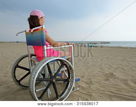 Little Girl On The Special Wheelchair With Big Wheels On The Sandy Beach In Summer