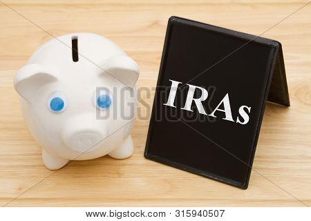 Knowing Your Ira Options, A Piggy Bank On A Desk With Chalkboard With Text Iras