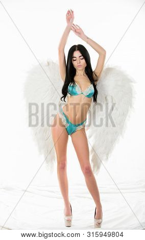 Erotic angel. Desirable and tempting lady. Impressive purity. Delicate sensual woman posing with angel wings. Fashion model. Girl wear lingerie and angel wings accessory. Femininity and sensuality poster