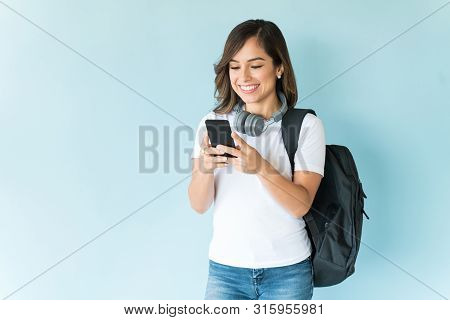 Smiling University Student With Backpack Using Mobile Phone Over Isolated Background