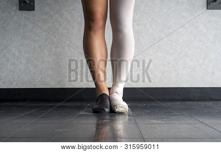 Dancer standing in parallel position at the barre, half dressed in Jazz dance attire and half in ballet attire poster
