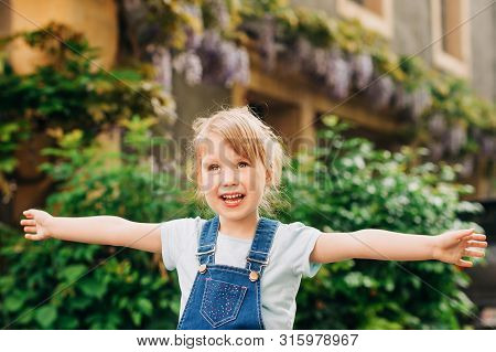 Outdoor Portrait Of Cute Little 3-4 Year Old Girl, Wearing Denim Pinafore, Arms Wide Open