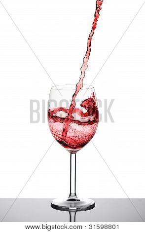 Red wine pouring into a glass of wine