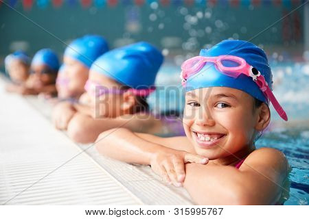 Portrait Of Children In Water At Edge Of Pool Waiting For Swimming Lesson