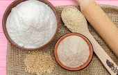 Whole grain rice flour and white rice flour in bowls. White rice, brown rice. The whole grain of rice. Unpolished rice in wooden spoon. Healthy food rice background. Row rice. Rice flour. Rice flour baking poster