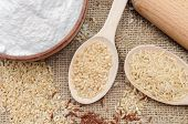 Rice flour in bowl, unpolished rice, brown rice in wooden spoon. The whole grain of rice. Unpolished rice and red rice on canvas background. Healthy food background. poster